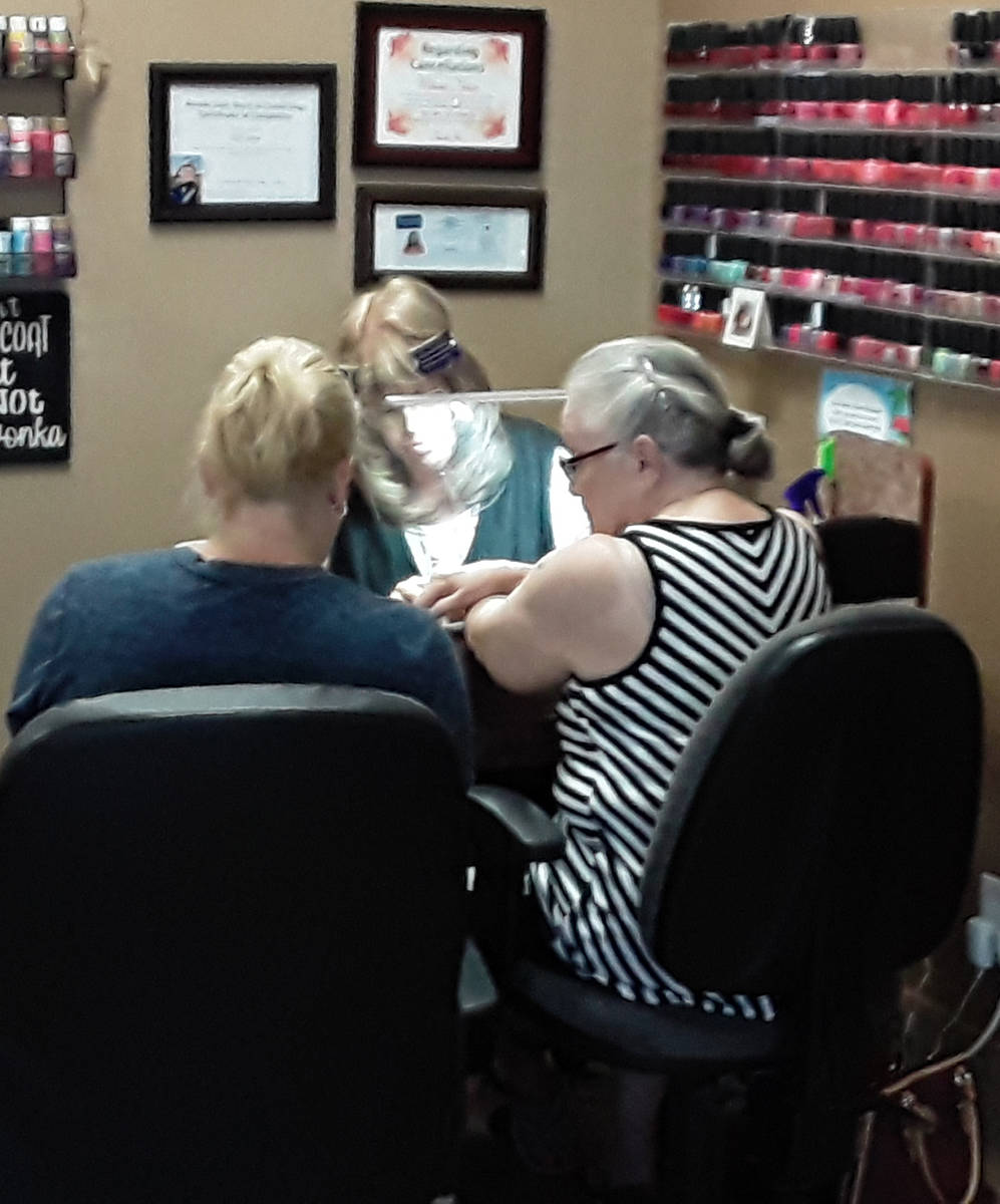 Selwyn Harris/Pahrump Valley Times A nail technician does her work while donning a full plastic ...