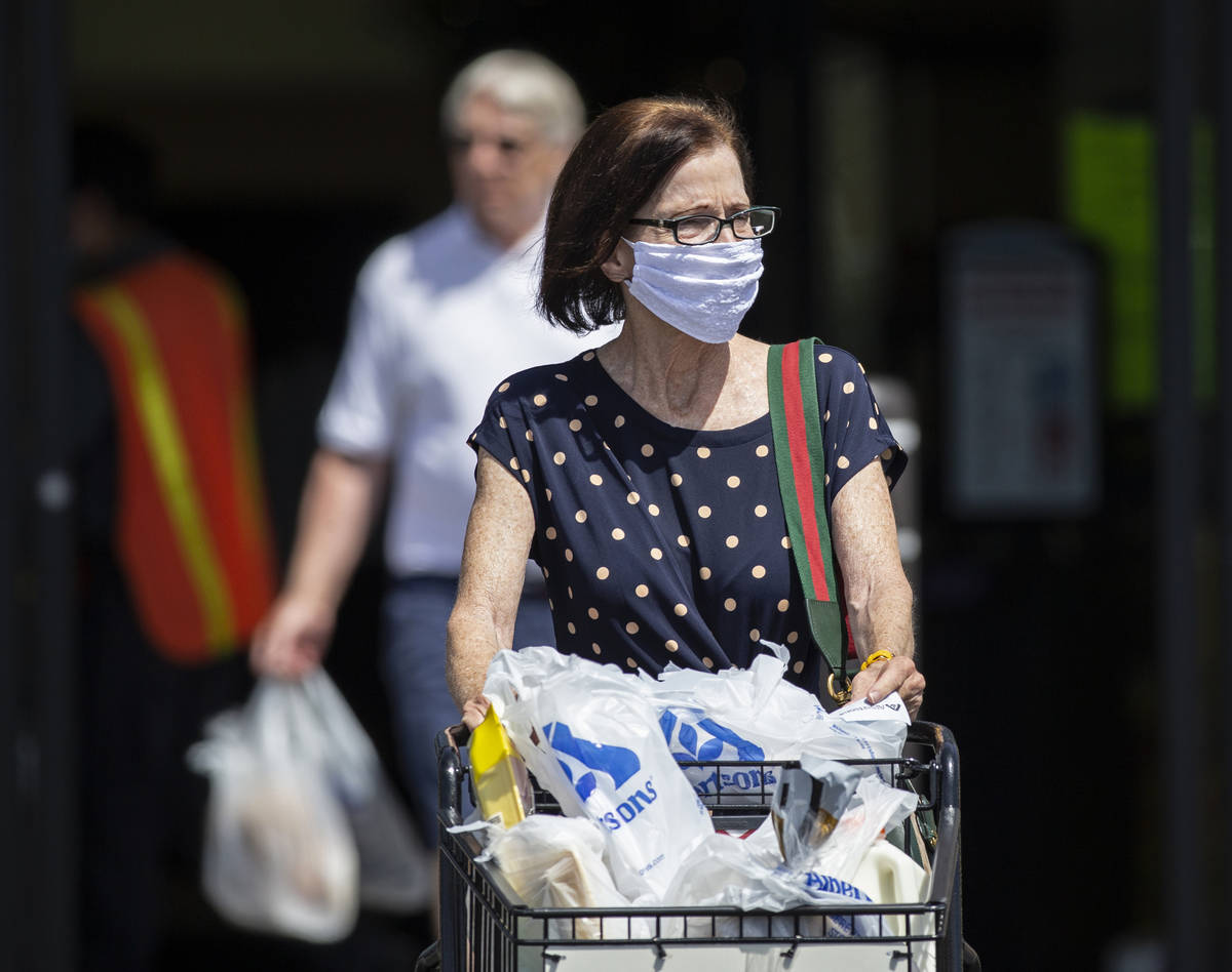 Benjamin Hager/Las Vegas Review-Journal Shoppers wear protective masks as they leave Albertsons ...
