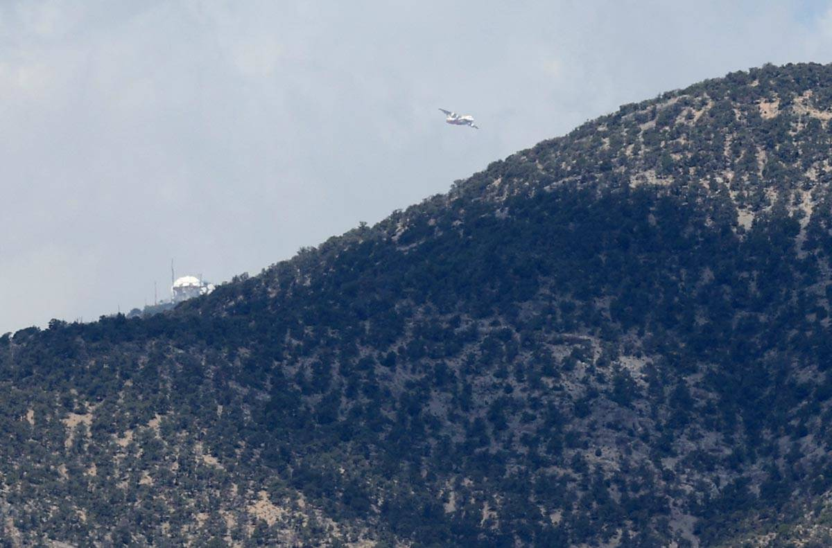 An air tanker circles after dropping fire retardant behind the ridge line while fighting the Ma ...