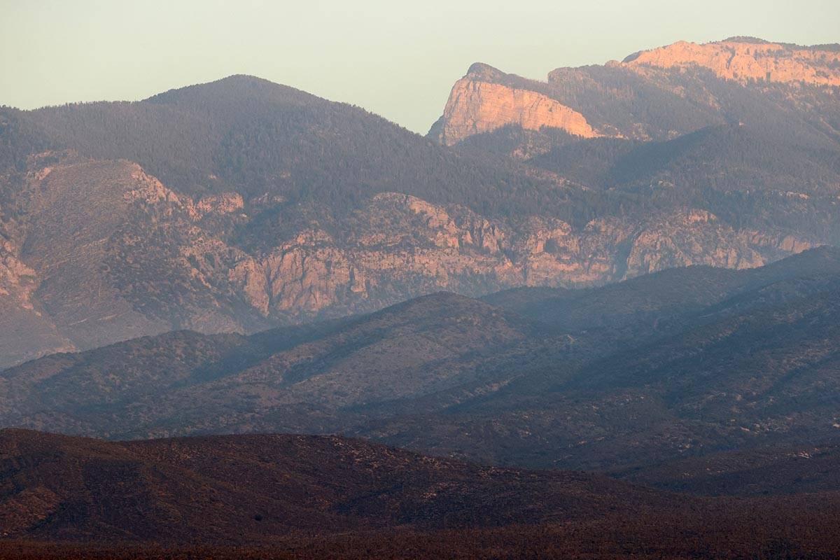 The sun rises on a ridgeline as crews battle the Mahogany Fire on Mount Charleston near Las Veg ...