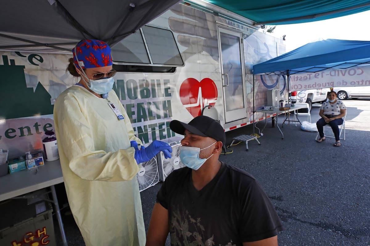 Nurse Tanya Markos administers a coronavirus test on patient Juan Ozoria at a mobile COVID-19 t ...