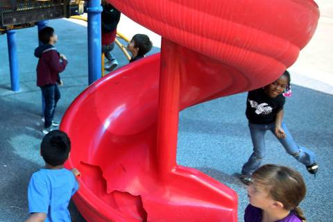 Students run around a broken slide in the playground at Helen Smith Elementary School in Las Ve ...