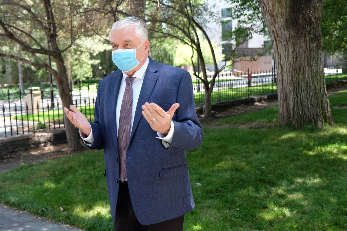 A masked Gov. Steve Sisolak speaks to reporters outside the Capitol discussing spending cuts an ...