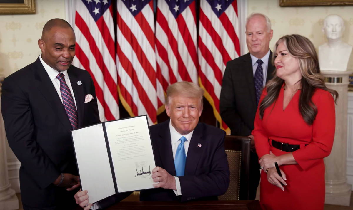 White House President Donald Trump holds up the pardon he gave Tuesday to Jon D. Ponder, left, ...