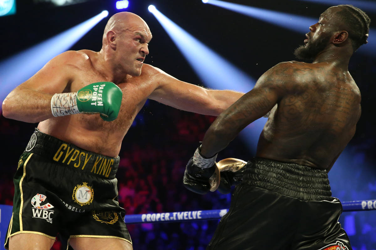 Deontay Wilder slips under Tyson Fury in round 4 of the WBC world heavyweight championship bout ...