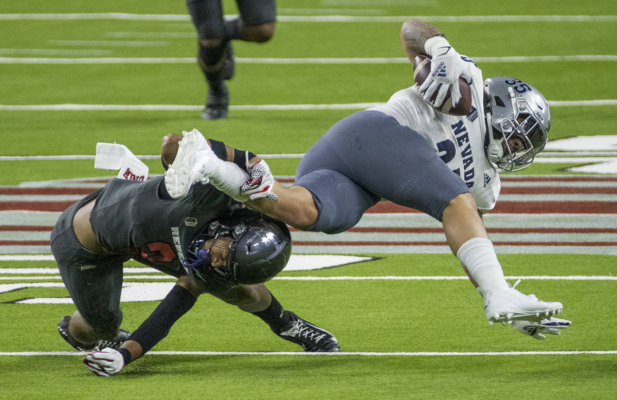 L.E. Baskow/Special to the Pahrump Valley Times UNR running back Toa Taua, right, is taken down ...