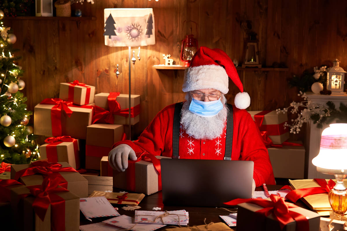 Old bearded Santa Claus wearing face mask, holding gift box on xmas eve sitting at cozy home ta ...