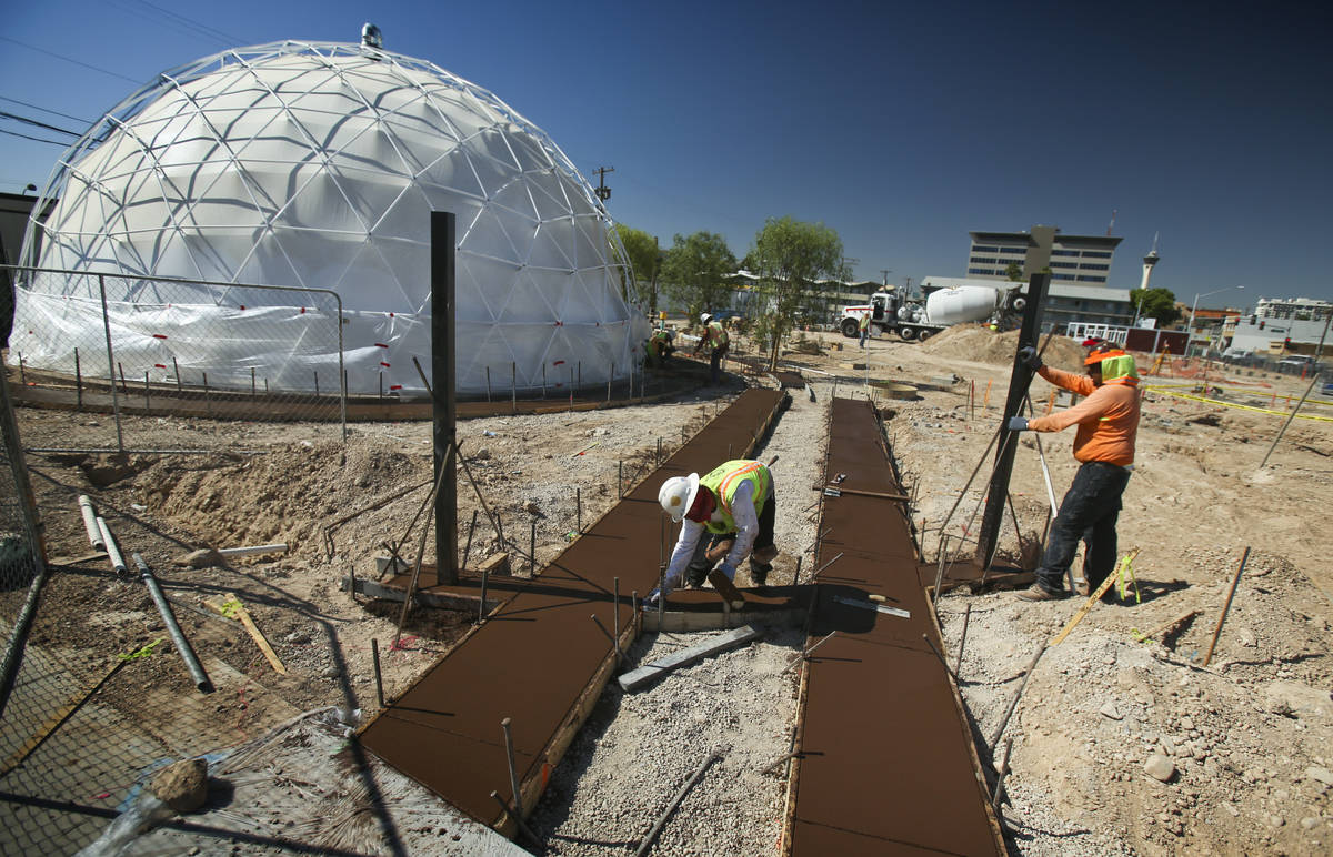 Men work on freshly poured concrete at Container Park, along Fremont Street and Seventh Street ...