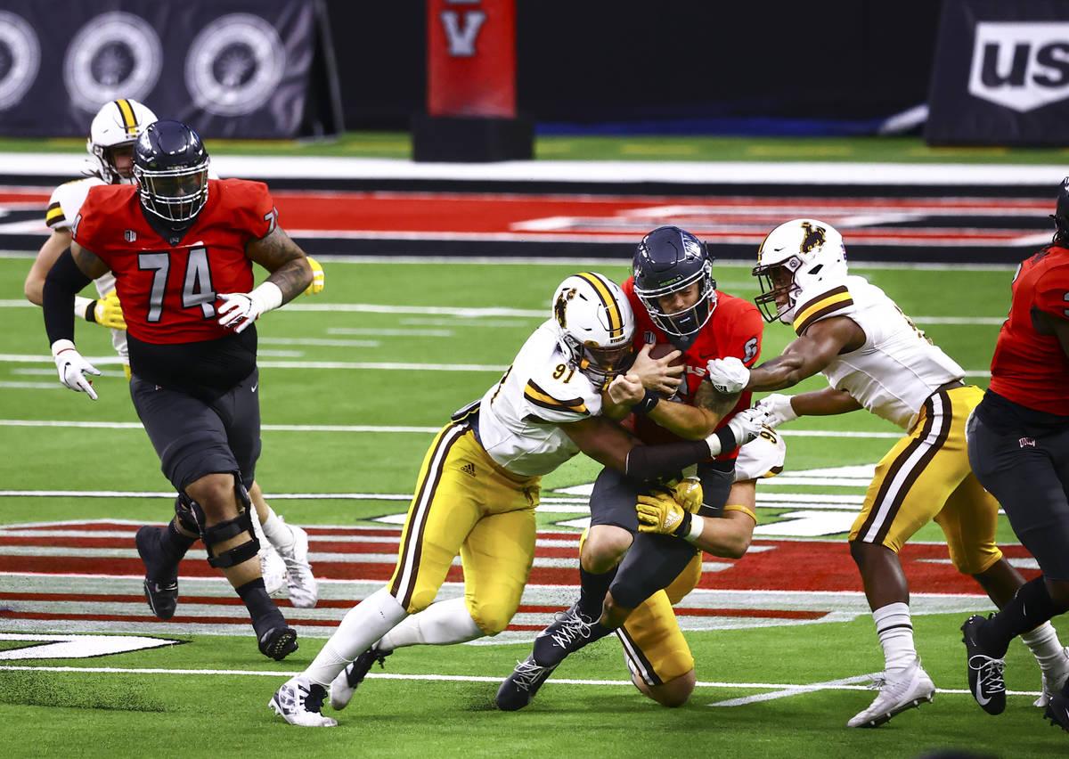 UNLV Rebels quarterback Max Gilliam (6) gets taken down by Wyoming Cowboys defensive end Jaylen ...