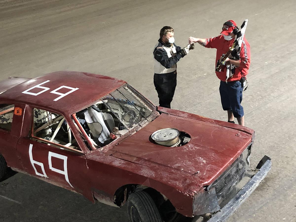 Tom Rysinski/Pahrump Valley Times Pahrump Valley Speedway flagman Dale Geissler congratulates J ...