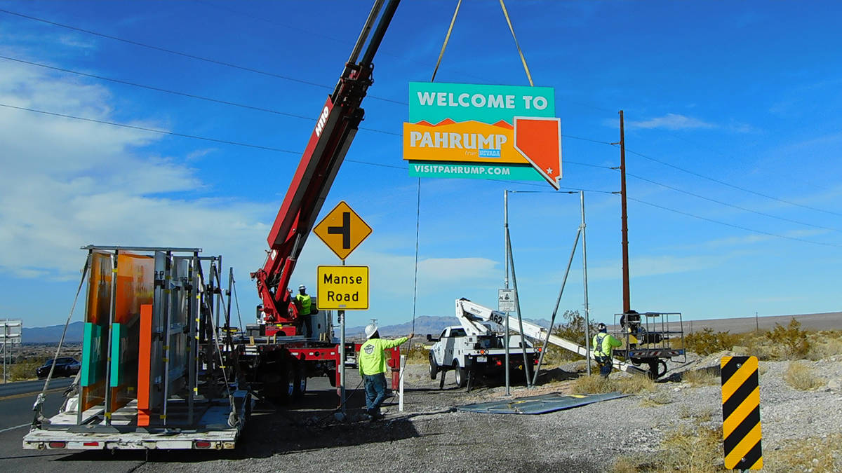 """Robin Hebrock/Pahrump Valley Times High Impact Signs and Designs is pictured installing a new """" ..."""