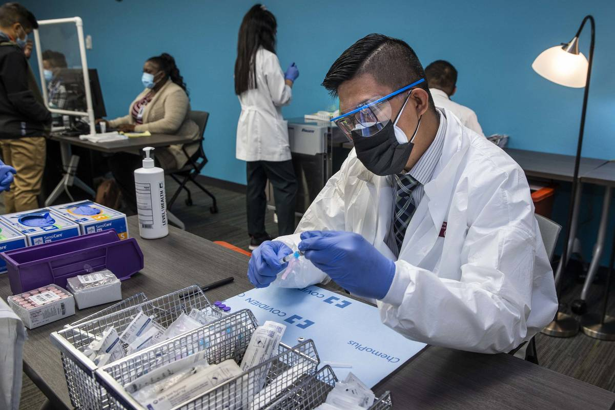 Student pharmacist Wilbur Quimba loads up new syringes with vaccine as University Medical Cente ...