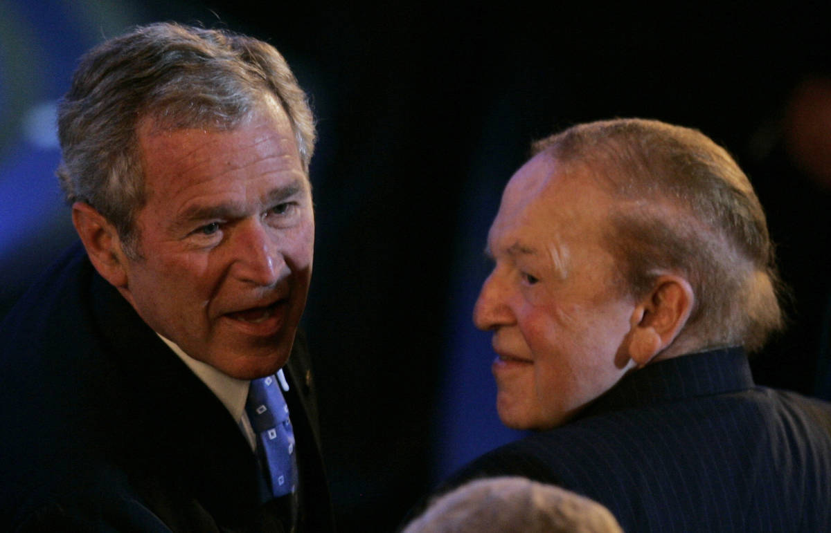 U.S. president George W. Bush, left, sits next to American businessman Sheldon Adelson, right, ...