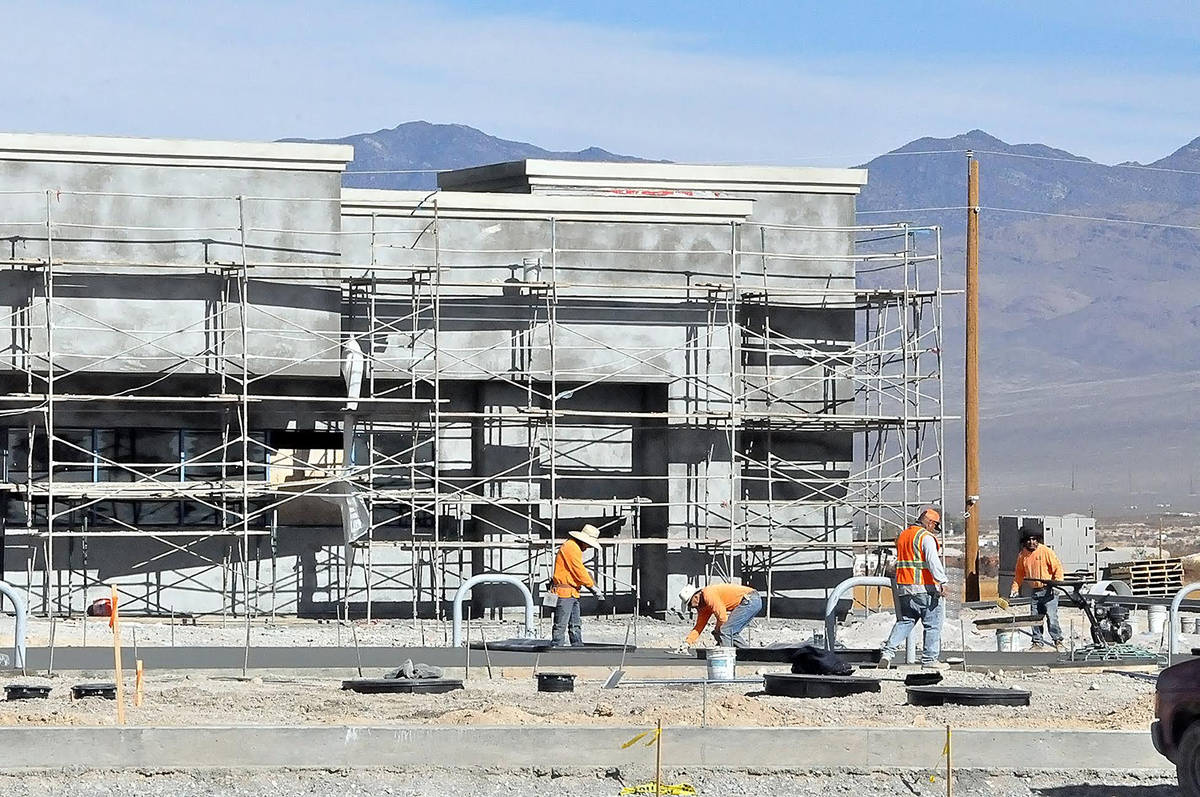 Horace Langford Jr./Pahrump Valley Times MO Construction workers are seen performing concrete w ...