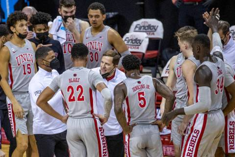 UNLV Rebels head coach T. J. Otzelberger counsels his players during a timeout versus the New M ...