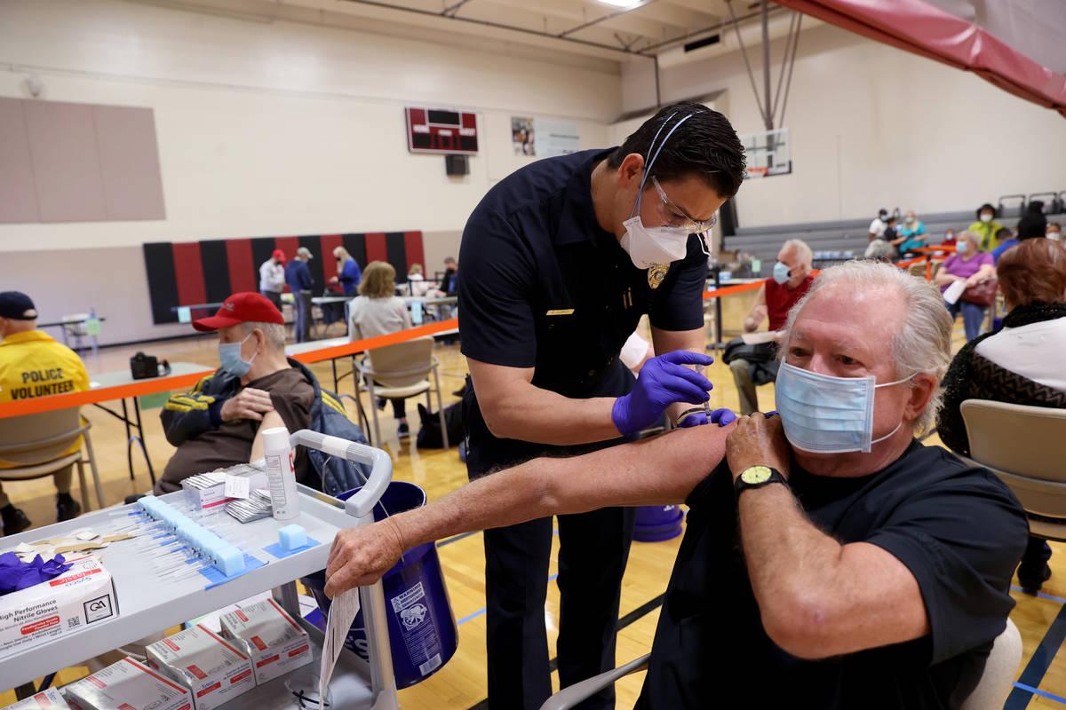 Las Vegas Fire Department firefighter Enrique Lopez vaccinates David Belding, 75, of Las Vegas, ...