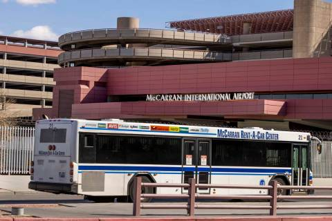 A rental car transport bus passes the Terminal 1 baggage area at McCarran International Airport ...