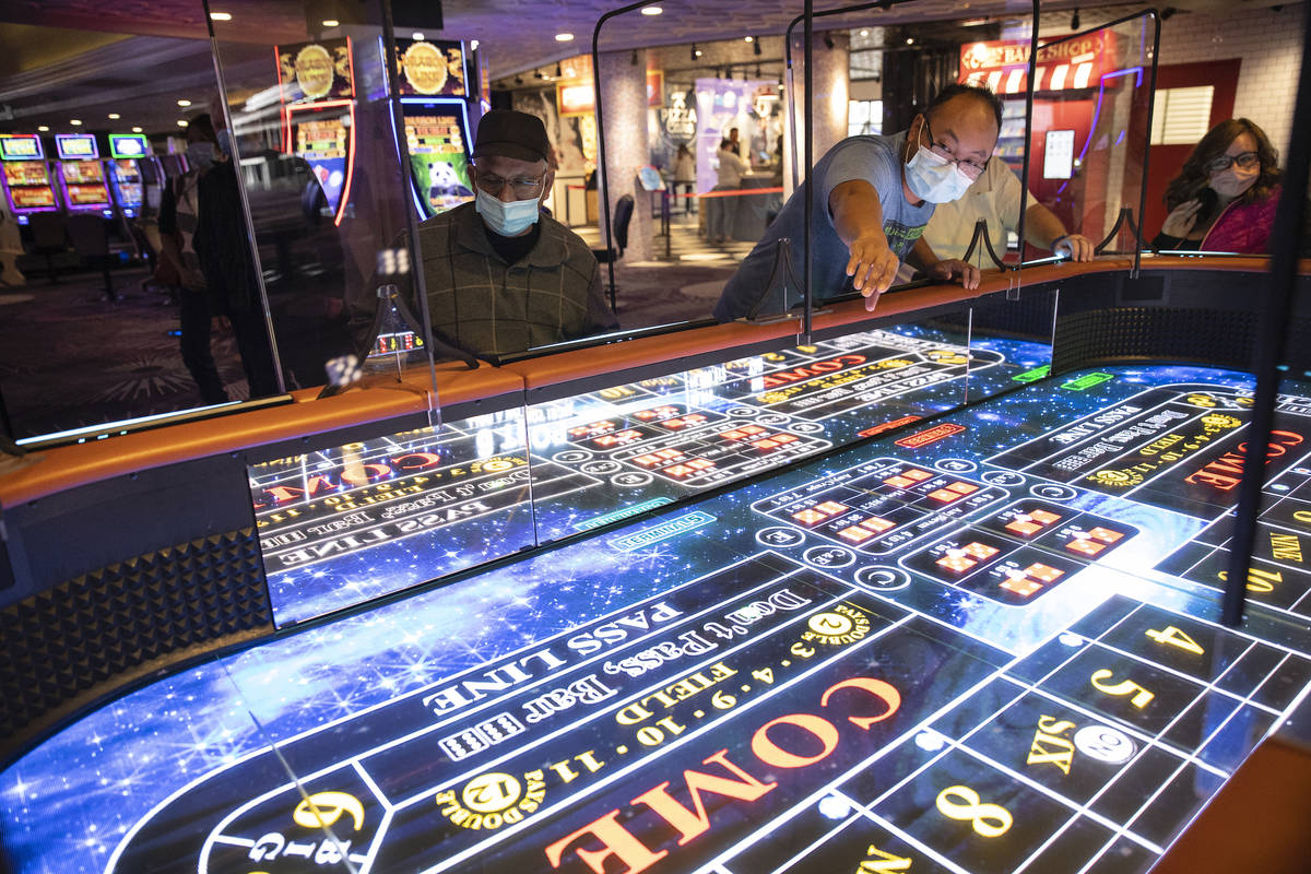 Rio Bencito of Los Angeles rolls dice on the new digital craps table, Rolls to Win Craps, at th ...