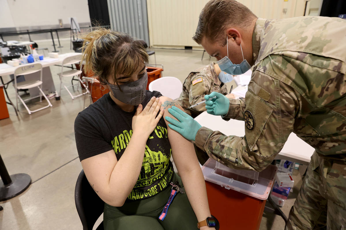 Micah Haji-Sheikh, 27, of North Las Vegas receives the COVID-19 vaccine from Nevada National Gu ...