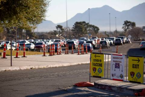 Signs indicate where to go to get a COVID-19 vaccine with a full parking lot in the background ...