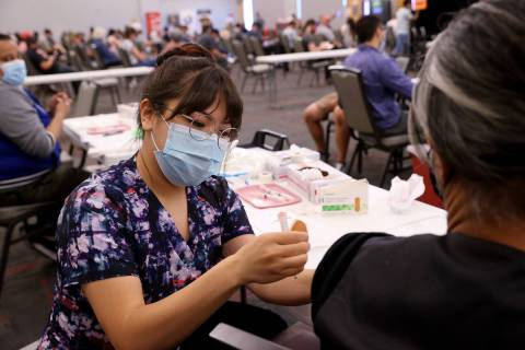 K.M. Cannon/Las Vegas Review-Journal Deanna Chea of UNLV Medicine gives a COVID-19 shot at the ...