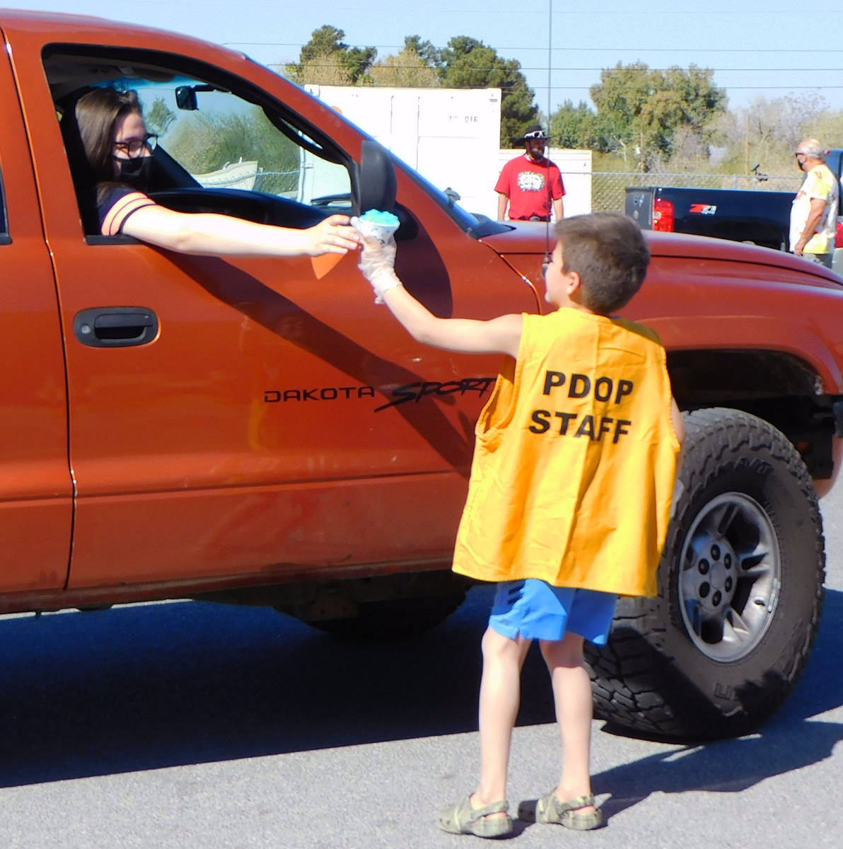 Robin Hebrock/Pahrump Valley Times A young PDOP volunteer is seen handing a snow cone to a Comm ...