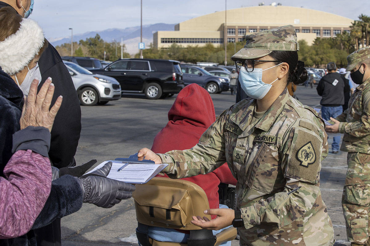 L.E. Baskow/Las Vegas Review-Journal PFC Wendy Garcia passes out paperwork as people wait in li ...