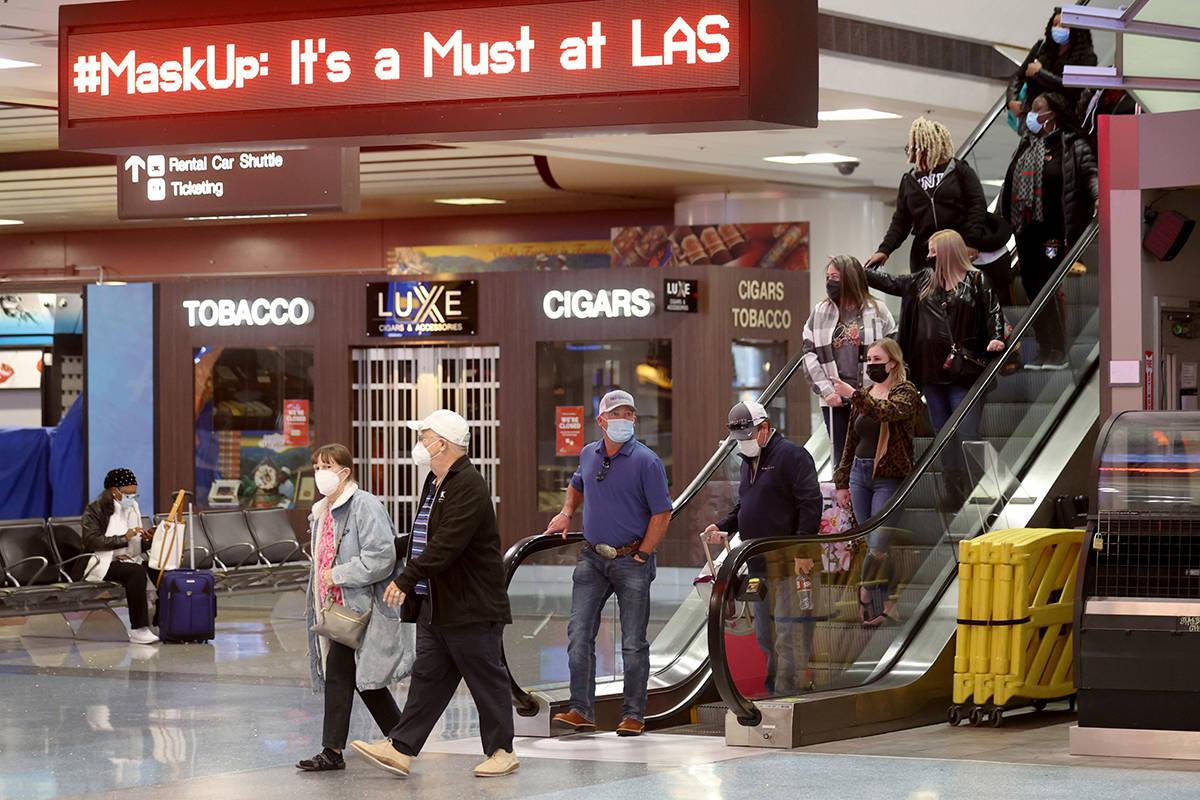 K.M. Cannon/Las Vegas Review-Journal Masked travelers walk through Terminal 1 at McCarran Inter ...