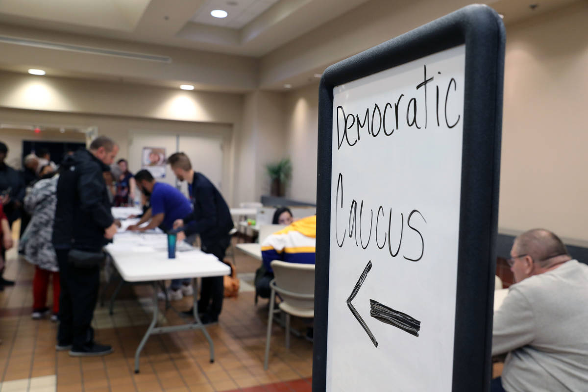 Individuals wait in line to register to caucus at the East Las Vegas Community Center in Las Ve ...