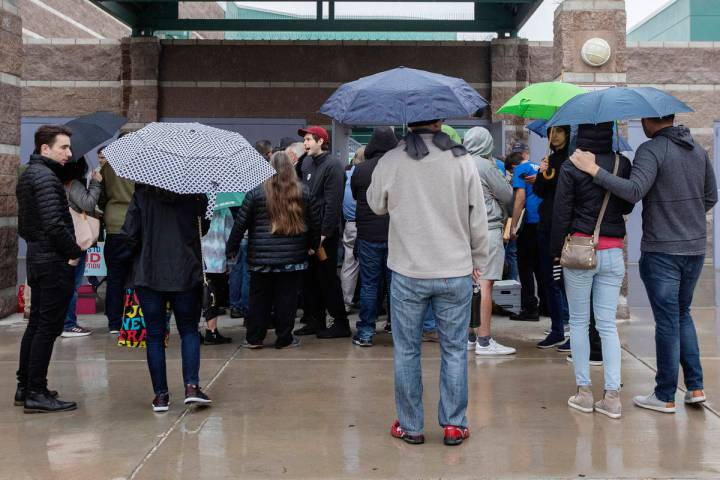 Caucusgoers and volunteers try to escape the rain before the Nevada caucus at Palo Verde High S ...