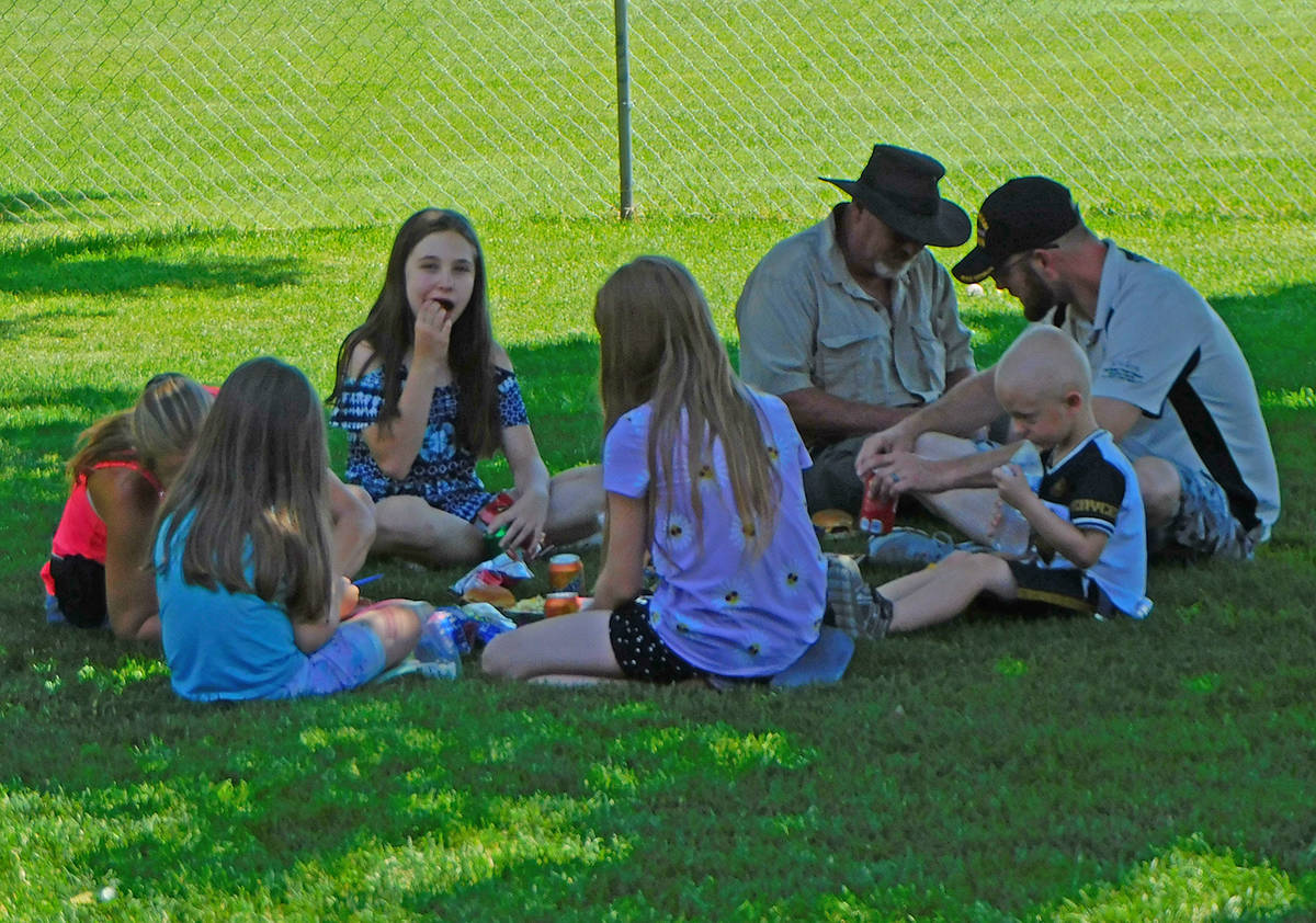 Robin Hebrock/Pahrump Valley Times A family is pictured sitting in the shade beneath a tree to ...