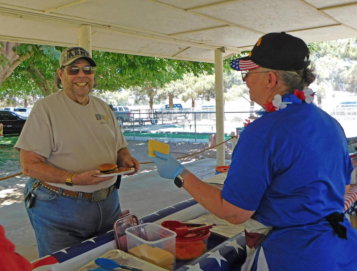 Robin Hebrock/Pahrump Valley Times Local veteran Richard Goldstein, left, is served a slice of ...