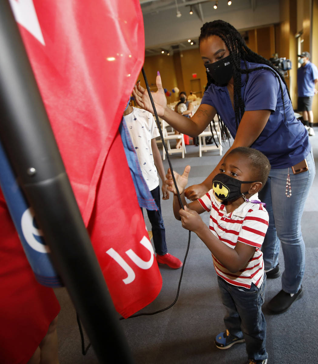 Jacobi Holmes, 4 of Las Vegas tires to raise a Juneteenth flag with his mother Kimberly Carter ...