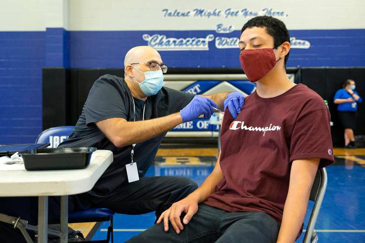Nurse Christian Hyderkhan administers the Pfizer COVID-19 vaccine to high school senior Edwin G ...