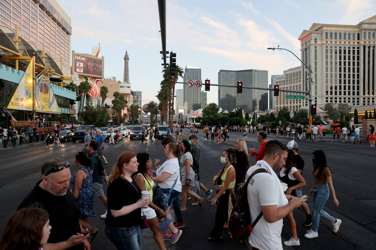 Crowds cross the Strip at between the Linq Promenade and Caesars Palace in Las Vegas Friday, Ma ...