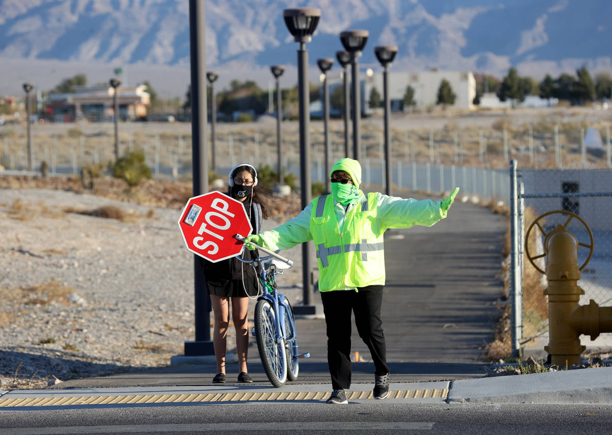 Crossing guard Mary Turner helps a Somerset Academy student at a crosswalk on Lone Mountain Roa ...