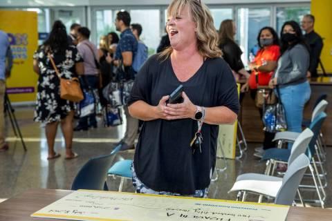 Teacher Elizabeth Allder laughs after her husband won $250,000 as Governor Steve Sisolak and Im ...