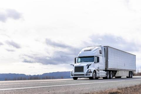Powerful long haul big rig industrial grade diesel semi truck transporting commercial food carg ...