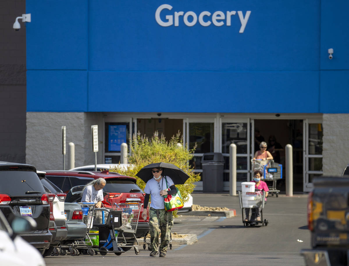 Shoppers make their way through a Walmart parking lot, most not wearing mask, on Friday, July 1 ...
