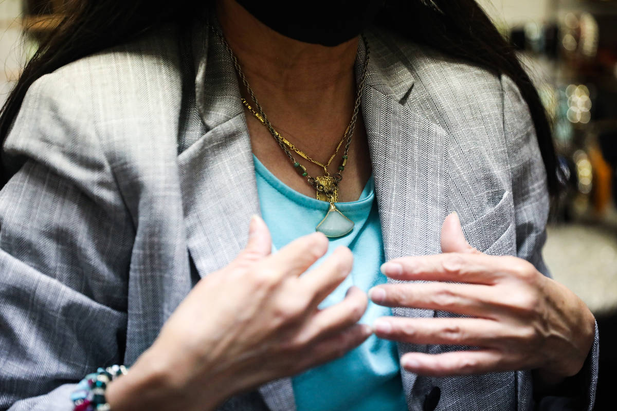 Nancy Sonano, right, tries on a necklace for her outfit at Dress For Success in Las Vegas, Tues ...
