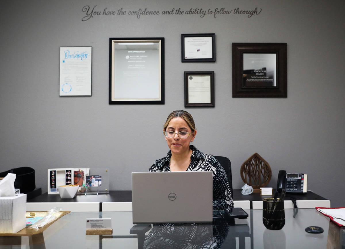 Norma Intriago, executive director of Dress For Success of Southern Nevada, works at her desk a ...