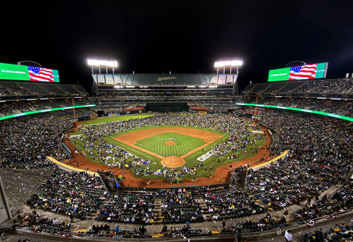 Fans take to the field to watch fireworks following the game of the Oakland A's against the B ...