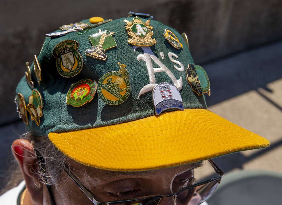 An Oakland A's fan sports a variety of pins on his hat as they battle the Texas Rangers at th ...