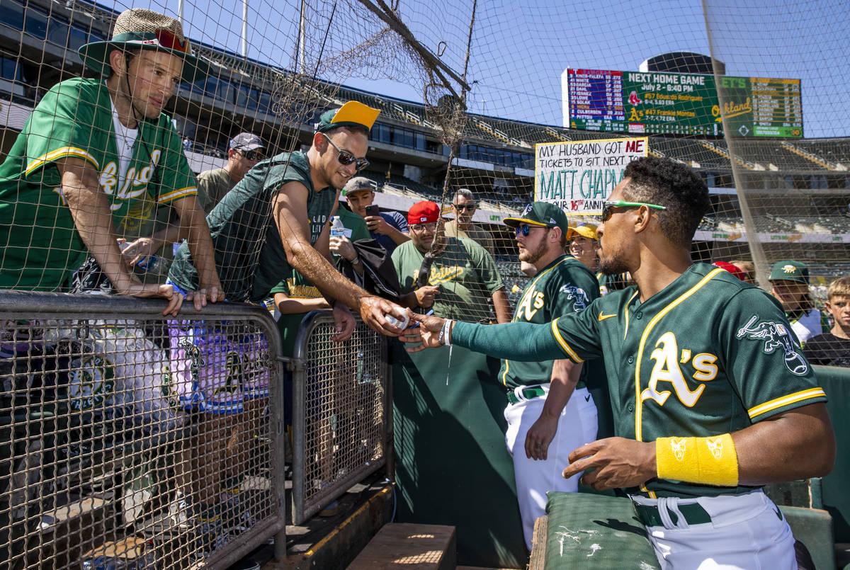 Oakland A's infielder Tony Kemp (5, left) and pitcher J.B. Wendelken (57) sign autographs for ...