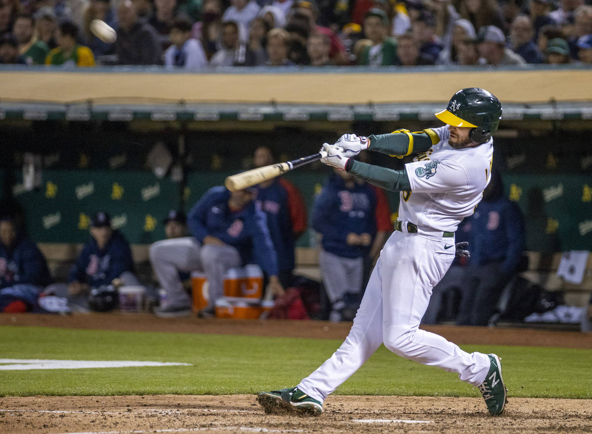 The Oakland A's infielder Jed Lowrie (8) hits a home run against the Boston Red Sox at RingCe ...