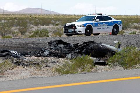Law enforcement officers investigate a plane crash on U.S. Highway 95, around the Nye County bo ...