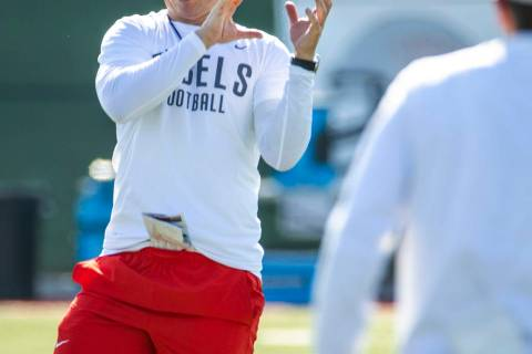 UNLV Head Coach Marcus Arroyo catches a pass from a quarterback during a drill in football team ...