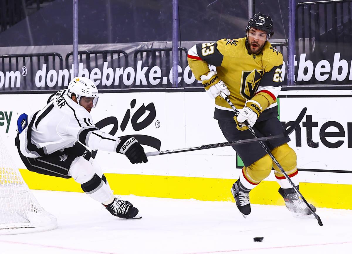 Golden Knights defenseman Alec Martinez (23) skates with the puck under pressure from Los Angel ...