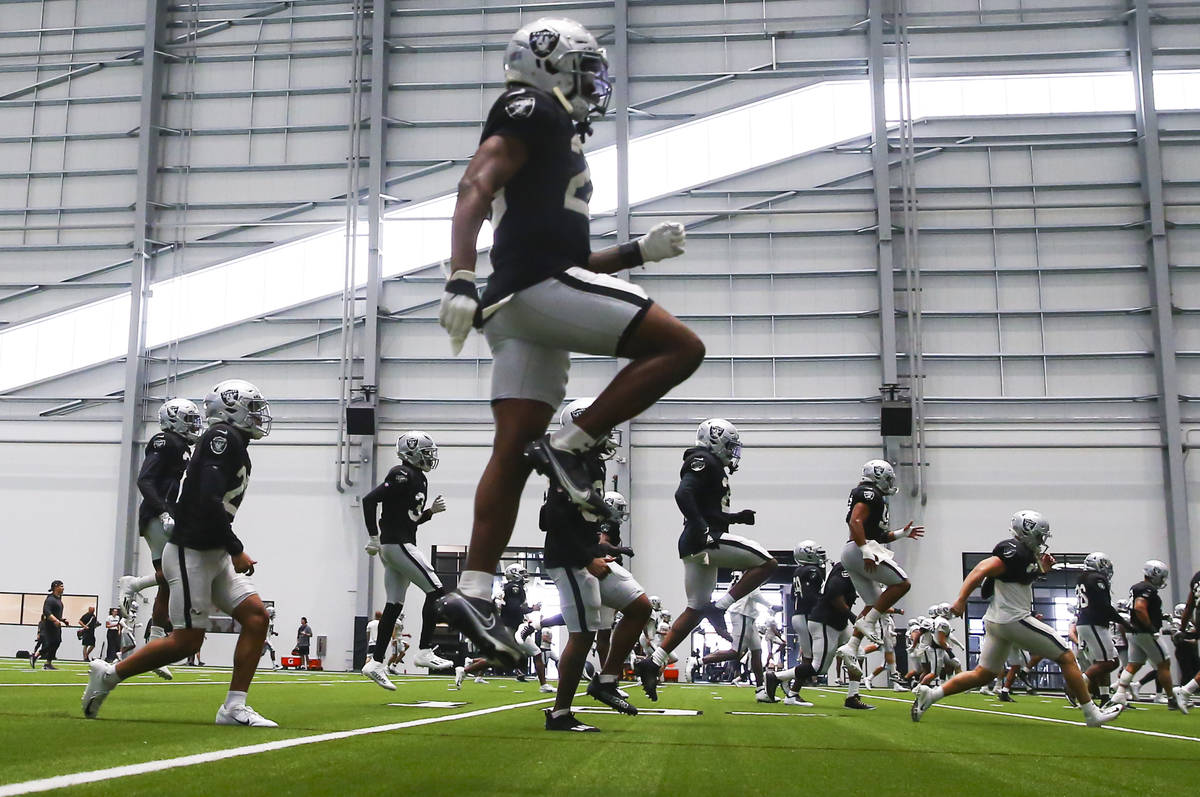 Raiders cornerback Nevin Lawson, above, warms up with teammates during training camp at Raiders ...