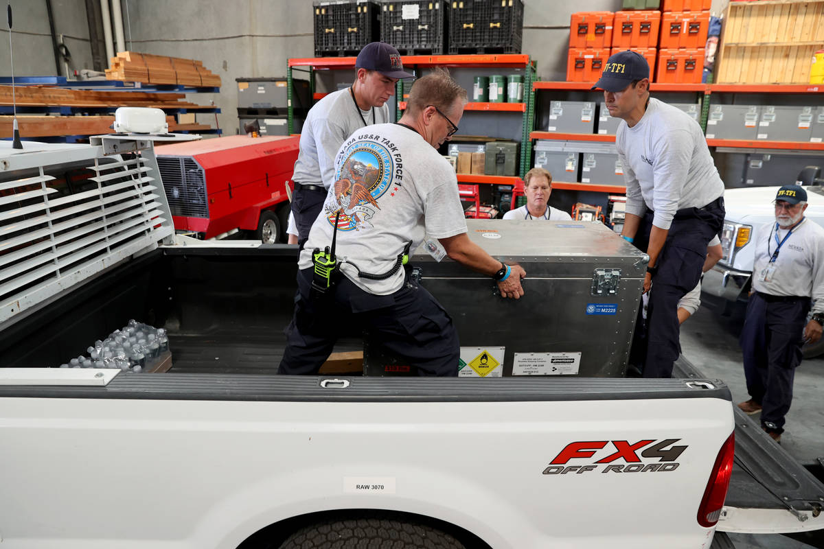 Members of the FEMA Nevada Task Force 1 Urban Search & Rescue team load equipment at their ...